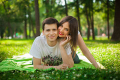 Young lovers out in the park lying on the grass Stock Images