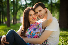 Young lovers out in the park lying on the grass Royalty Free Stock Photography