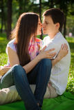 Young lovers out in the park lying on the grass Stock Photos
