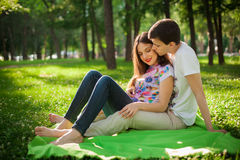 Young lovers out in the park lying on the grass Royalty Free Stock Images