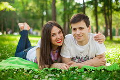 Young lovers out in the park lying on the grass Stock Image