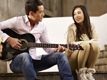 Young lovers playing guitar and singing. Young asian lovers sitting on steps playing guitar and singing Stock Images