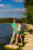 Young lovers. On the rocks by the sea and enjoy each other Stock Images