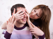 Young lovers in the room. Attractive couple posing on background of wall Stock Photo