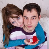 Young lovers in the room. Attractive couple posing on background of wall Royalty Free Stock Images