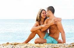 Young lovers  at sandy beach Stock Photos