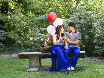 Young Lovers sharing red wine while sitting on log bench outdoor Royalty Free Stock Photography