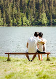Young lovers sitting on wooden bench Stock Photo