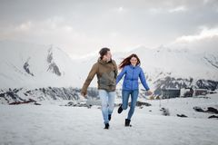 Young lovers spending time and having fun in mountains. Young lovers spending time and having fun walking and laughing in high mountains covered with snow royalty free stock photography