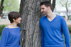 Young lovers supported on a  tree at the park Royalty Free Stock Images