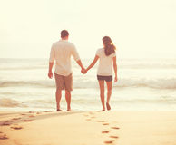 Young Lovers Walking Down the Beach at Sunset Royalty Free Stock Images