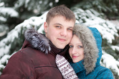 Young lovers woman and man in  winter forest Royalty Free Stock Photos