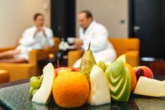 Young loving Caucasian honeymoon couple of man and woman in white bathrobes drinking tea and talking after spa with different fres. H fruits on table on Royalty Free Stock Photography