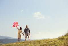 Young loving couple with balloons. On sky background Stock Photography