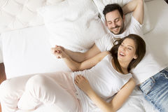 Young loving couple in the bed Stock Photos