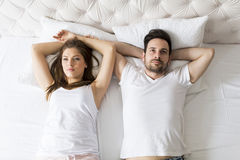 Young loving couple in the bed. Young loving couple lying on their backs in the bed royalty free stock image