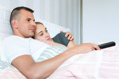 Loving couple in bed, watching television together Stock Images