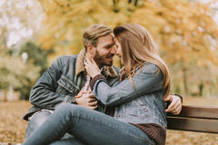Young loving couple on the bench in the autumn park Stock Photo