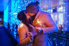 Young loving couple burning sparklers by holiday illumination. Christmas and New year concept royalty free stock photos