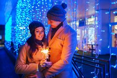 Young loving couple burning sparklers by holiday illumination. Christmas and New year concept royalty free stock photo