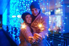 Young loving couple burning sparklers by holiday illumination. Christmas and New year concept stock photo