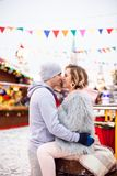 Young loving couple Caucasian kissing outside at the winter fair royalty free stock photos