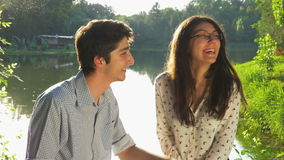 Young loving couple chatting in the park stock video