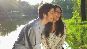 Young loving couple chatting in the park stock video footage