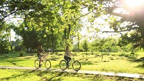 Young loving couple dating while riding bicycles in the park.  stock video footage