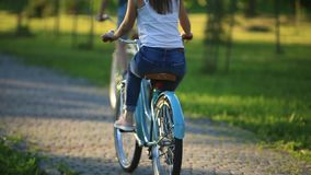 Young loving couple dating while riding bicycles in the park.  stock video