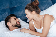 Young loving couple embrace in bed Stock Photos