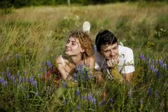 Young loving couple enjoying nature, holding hands and walking on the field with lavender. Beautiful people on nature in spring at royalty free stock photos