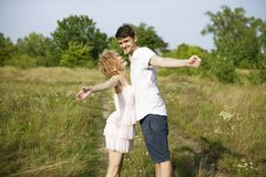 Young loving couple enjoying nature, holding hands and walking on the field with lavender. Beautiful people on nature in spring at stock photo
