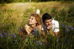 Young loving couple enjoying nature, holding hands and walking on the field with lavender. Beautiful people on nature in spring at. Young couple enjoying nature stock photos