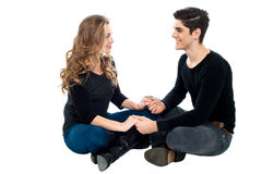 Young loving couple on floor holding hands Stock Images