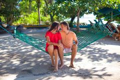Young loving couple in a hammock in exotic resort Stock Photos