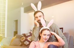 Young loving couple having fun with pink rabbit ears on head. Happy family preparing for Easter. Young loving couple having fun with pink rabbit ears on head royalty free stock photography