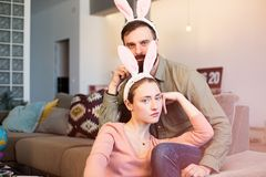 Young loving couple having fun with pink rabbit ears on head. Happy family preparing for Easter. Young loving couple having fun with pink rabbit ears on head royalty free stock photos