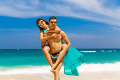 Young loving couple having fun on tropical beach. Summer vacatio Stock Images