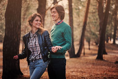 Young loving couple having fun on the walk in sunny forest Royalty Free Stock Images