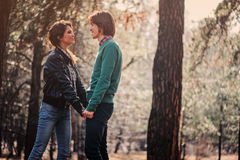 Young loving couple having fun on the walk in sunny forest Stock Photo
