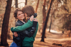 Young loving couple having fun on the walk in sunny forest Stock Photos