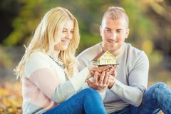 Young loving couple holding small model house stock photography