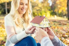 Young loving couple holding small model house. stock photos