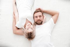Sensual young couple together in bed. Happy couple in bedroom  on a white background. Young loving couple hugging each other, smiling and posing on camera on Stock Photography