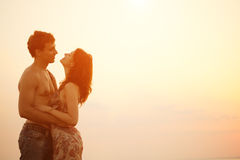 A young  loving  couple hugging and kissing on the beach at suns Stock Image