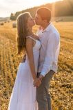 Young loving couple kissing in a field Royalty Free Stock Photo