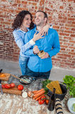 Young Loving Couple in the Kitchen Stock Images