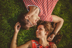 Young loving couple lying together head to head on a grass at summer. Both in red clothes and holding hands. Overhead top view stock photo