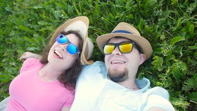 Young loving couple making selfie while lying on the grass stock video